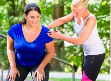 lady helping another lady with exercise